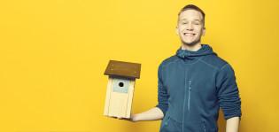 Poika pitää kädessään linnunpönttöä.