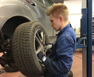 opiskelija vaihtaa auton renkaita