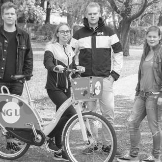 Neljä nuorta polkupyörän kanssa puistossa