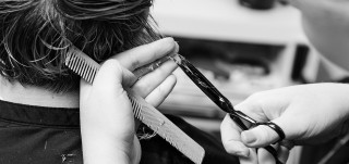 Kampaajaopiskelija leikkaa asiakkaan hiuksia
